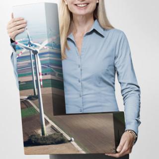 Frau hält größes L, welches eine Windtrubine zeigt