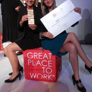 """2 Frauen sitzen auf eine Hocker (""""Great Place to Work"""") und halten Zertifikat"""