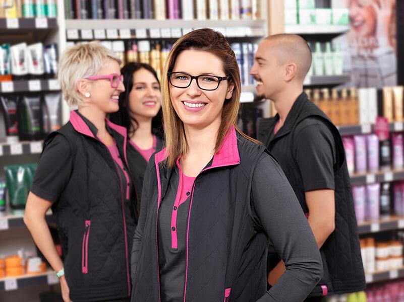 Portrait einer BIPA-Mitarbeiterin in der Filiale, dahinter 2 Mitarbeiterinnen und 1 Mitarbeiter im Gespräch
